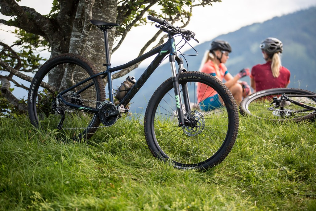 two women sitting next to mountain bikes and resting